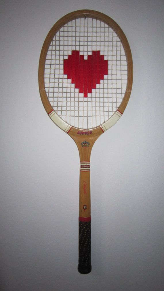 embroidered heart on vintage tennis racket as a wall decoration.