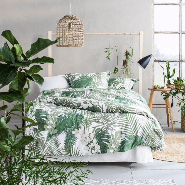 Une chambre lumineuse décorée dans un style tropical, très tendance cette année ! Les bonnes astuces déco à retenir : du linge de lit vert et blanc à motif feuilles, une tête de lit minimaliste en bois brut, une suspension en rotin, un tapis tressé et des plantes partout ! #tendance #deco #tropical #bonjourbibiche