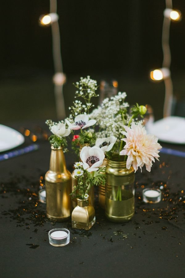 DIY these gold mason jars and throw in some seasonal flowers for a very pretty wedding day look. We love this centerpiece.