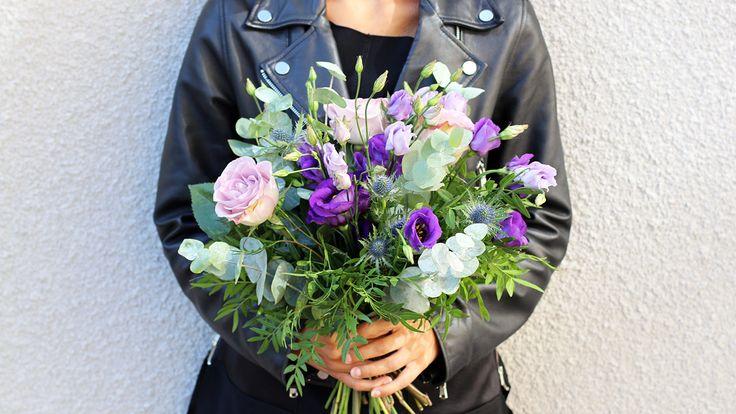 Blomsterprakt! Buketten innehåller tistlar, rosor, prärieklocka och frodigt grönt.
