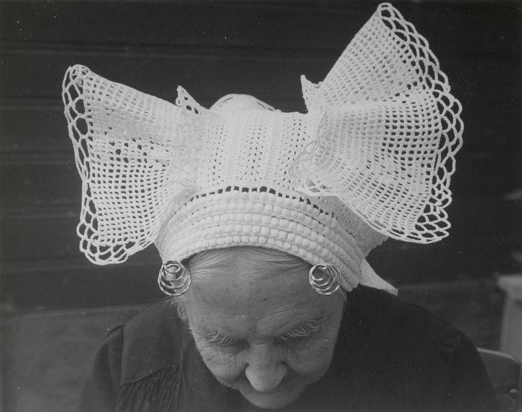 Weduwe Beurkens uit St. Philipsland met 'haakmuts' 1956 Weduwe Beurkens uit St. Philipsland (93 jaar) met 'haakmuts'. Onder deze gehaakte muts draagt zij een oorijzer met 'getorste krullen' (van getorst vierkant gouddraad). De slippen aan de achterzijde van de muts zijn gemaakt van machinaal vervaardigde slooptussenzetsels. Vroeger werden deze slippen gehaakt. #StPhilipsland #Zeeland