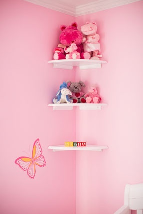 pink butterfly themed baby girl nursery room corner bookshelf loaded with fun stuffed animal toys