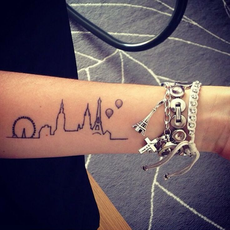 Little forearm tattoo of the skyline of Paris and London on Dani.