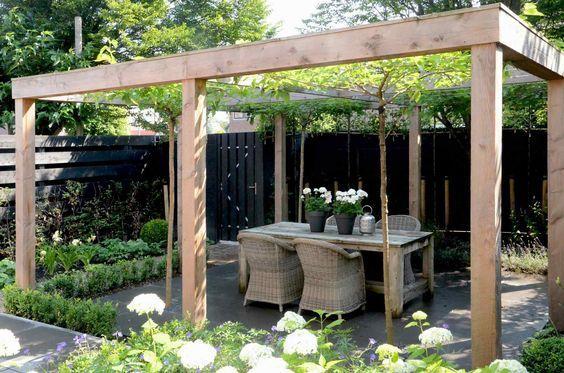 Een pergola is een klassiek element om een terras meer sfeer en intimiteit mee te geven. In dit voorbeeld wordt dat nog eens versterkt doordat dakbomen een groen dak vormen.