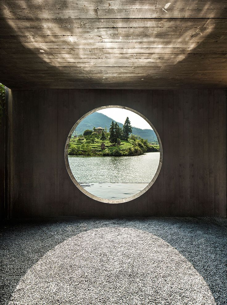 a series of concrete forms overlooking the waterfront contain tea houses of…