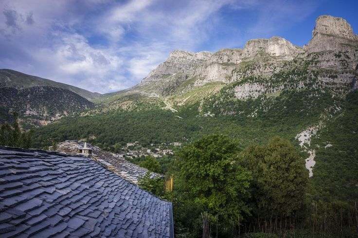 View of village slate rooftops with dramatic mountain scenery in background, Zagóri Greece.