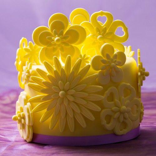 Deze gele zomertaart vol met bloemen is het ideale zomerse taartje! We hebben deze taart gevuld met een heerlijke frisse vulling. Na het bekleden van de taart, ga je aan de slag met de bloemendecoraties.