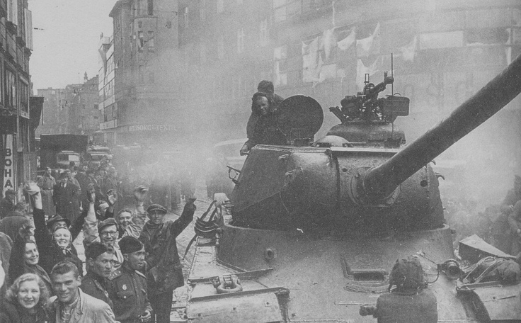 """Moravian Ostrava, Czechoslovakia, May 1945: Residents of the city celebrate the arrival of Russian tanks in the wake of headlong German retreat. The photo is obscured by the clouds of engine fumes generated by the Russian vehicles.Manufacturing standards were still eons away from """"environmentally friendly"""" requirements. Note the indestructible Degtyaryov-Shpagin Large-Caliber (DShK) heavy anti-aircraft machine gun on the tank turret."""
