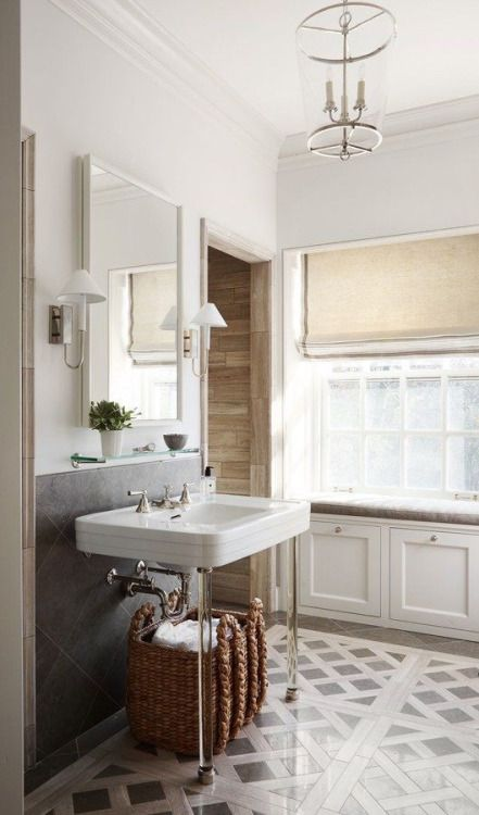 tile floor pattern storage under window seat and acrylic legged sink in this bathroom