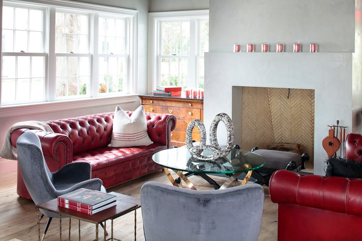 matching vintage red chesterfield couches, and notice the rustic leather wrapped fireplace tool set.
