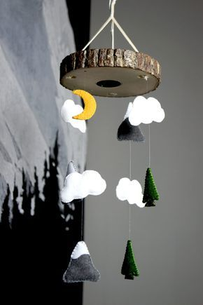 How cool! Hide the baby camera in your nursery in a mobile! This DIY nursery mobile tutorial shows how to incorporate a camera into a wood slice top as well as how to make an outdoor themed mobile made of felt mountains, clouds trees. The DIY nursery camera mobile is a fun DIY project and would be a great addition the nursery.