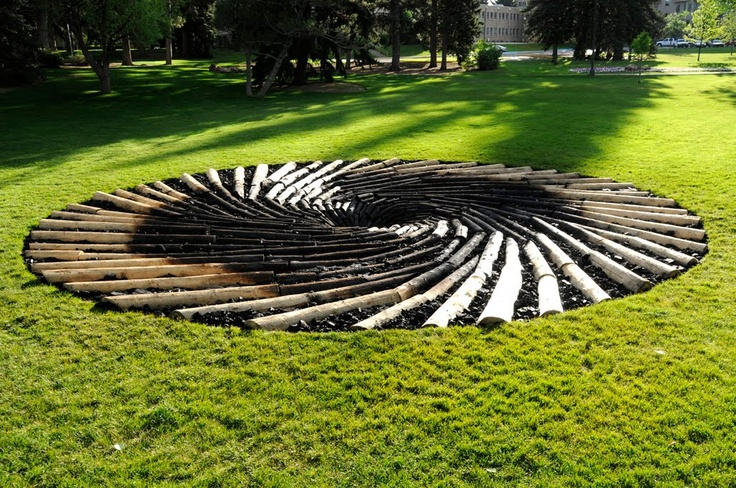 Carbon Sink: What Goes Around Comes Around.  Installation at the University of Wyoming by British artist Chris Drury. The sculpture, a 36-foot spiral of logs morphing into charred coal, is constructed from trees that have died from skyrocketing beetle infestations across the western United States.