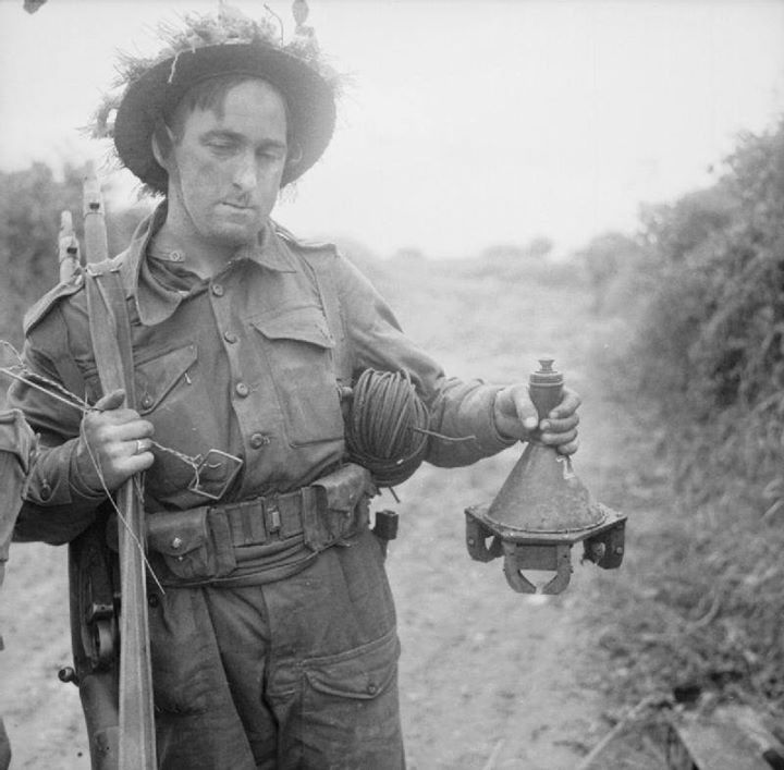 Lance Corporal Lodge of 278th Field Company British Royal Engineers holding a captured German 3 HL shaped charge near Caen France 26 June 1944.