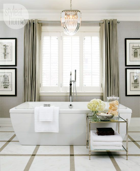 A 1940s Lucite pendant light hangs over the bathtub.  The walls are covered in vinyl grasscloth wallpaper in a soft grey color-more practical in a bathroom than the real thing. Vintage architectural prints in sleek black frames and off-white mats suits the tailored aesthetic.    Harvey designed a Burberry-inspired floor from 18-inch-square Calacatta marble tiles bordered by linear limestone and small dark blue-grey stone laid in a plaid pattern that helps shrink the visual scale of the room.
