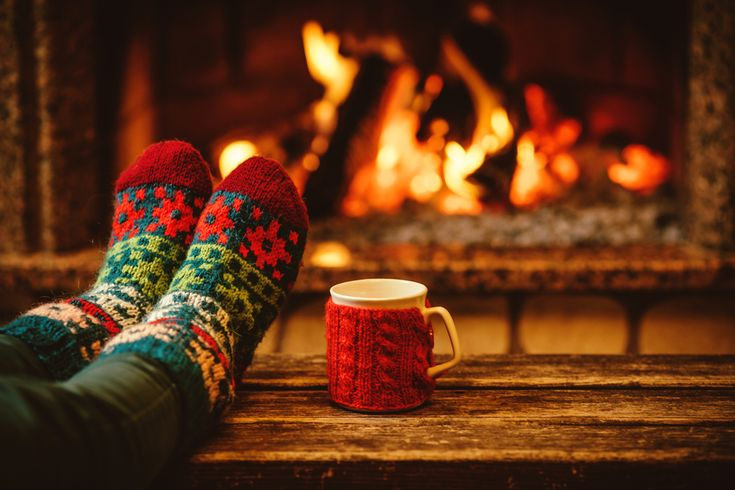 A pair of feet in wool socks relaxing in front of the fireplace with a mug of hot chocolate in a cabin.