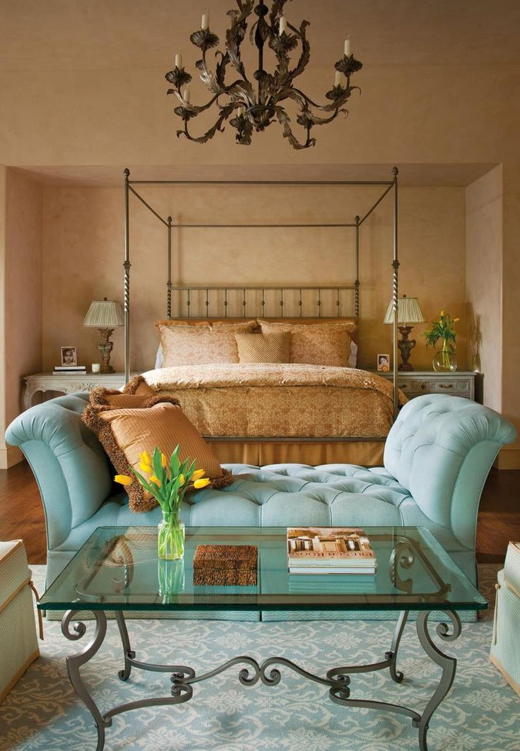 A four-poster bed with a heavy iron chandelier occupy this master bedroom suite. The tufted turquoise chaise and glass coffee table create a small seating ... : in a chaise and four - Sectionals, Sofas & Couches