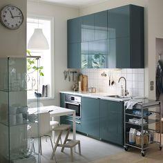 Une petite cuisine moderne avec murs blancs et portes en gris-turquoise brillant.