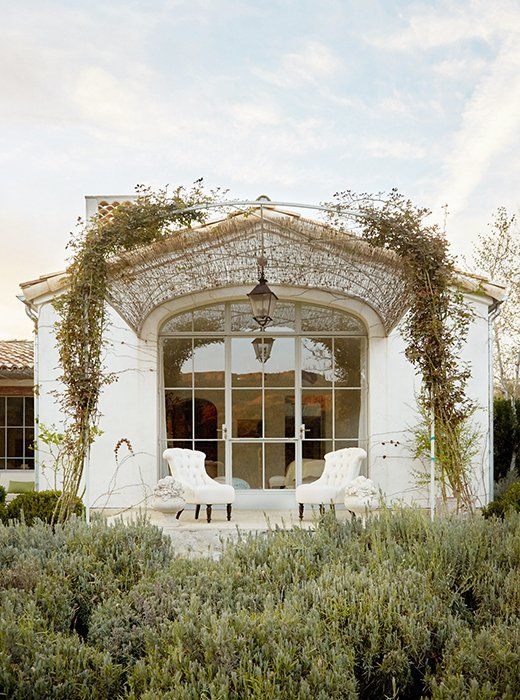 """One wall of the master suite leads to a stone porch. """"We like to create outdoor extensions to as many rooms as possible,"""" says Brooke. An arched steel trellis with some reed fencing drapes a pair of upholstered chairs from Giannetti Home."""