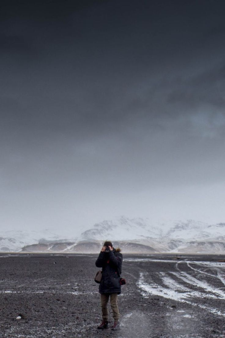 Man Standing on Gray Dessert Under Gray Cloudy Sky during Daytime
