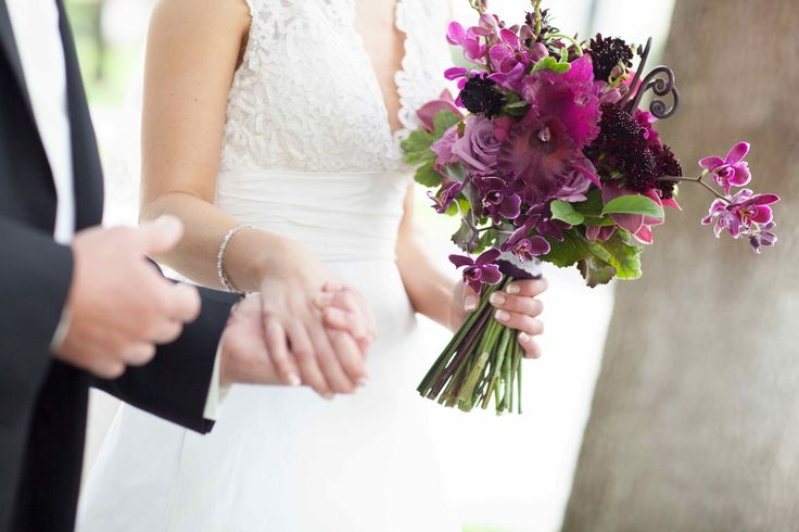 the bride's bouquet reflected her love of rich purple hues. purple catleya orchid, purple dendrobium orchid, purple cymbidium orchid, burgundy dahlia, cool water roses, burgundy scabiosa, geranium leaf, lemon leaf, galax leaf and monkey tail fern was hand tied with a piece of lace from her mother's wedding gown.
