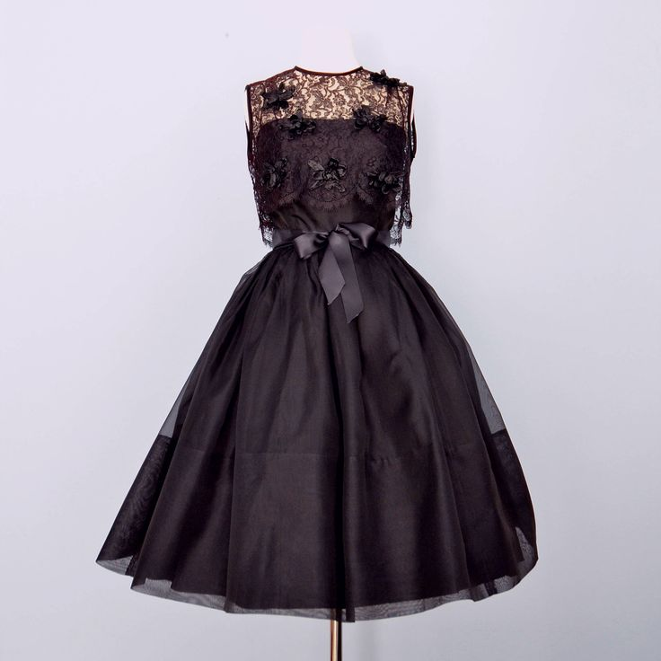 Prachtige vintage 1960s zwarte partij jurk heeft een verwisselbare lace jas. Ingerichte bodice. Dunne bandjes. Trim taille. Super volledige rok. Volledige terug nylon rits. Volledig gevoerd. Mouwloos lace jas heeft een geschulpte zoom en satijn trim op de hals en armsgaten. Jas is geaccentueerd met zwarte raffia bloemen.  Gefotografeerd met een crinoline, die niet inbegrepen is.  Label - geavanceerde Miss  Jurk: Buste - 32 inch Taille - 25 inch Heupen - Full Schouder taille - 15 1/2 inch...