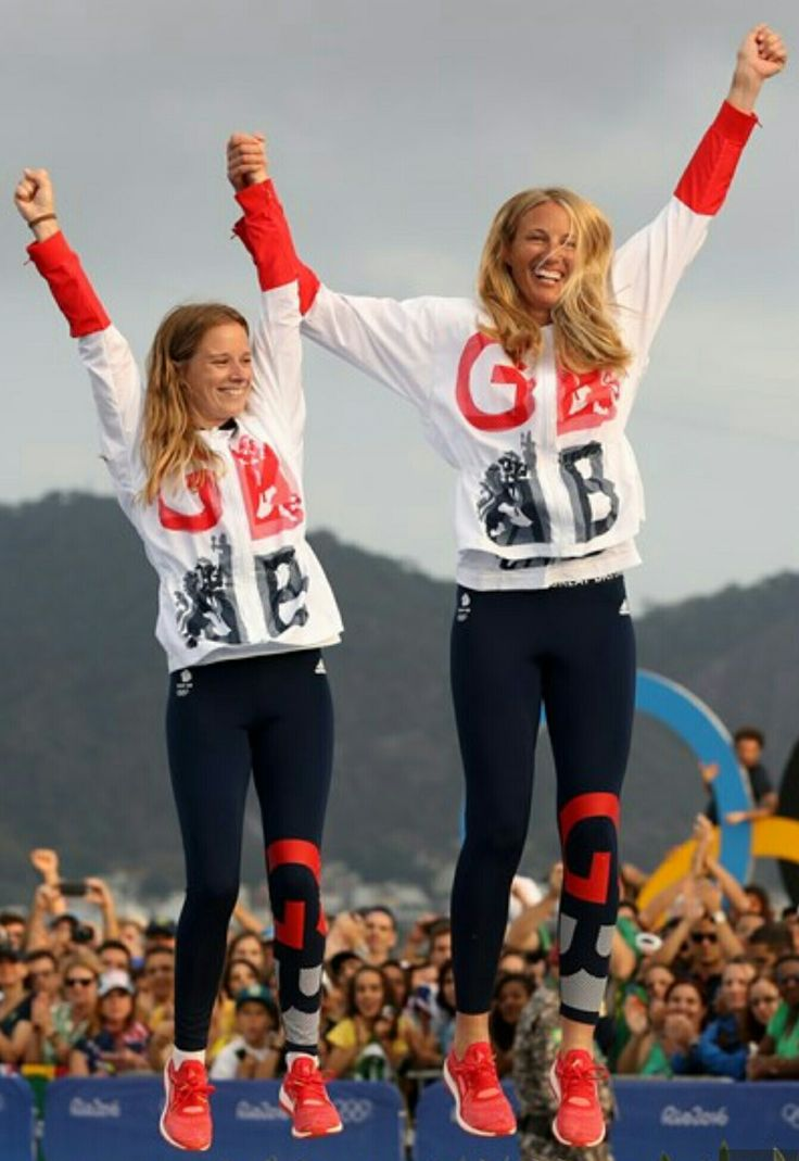 Hannah Mills and Saskia Clark, of Great Britain, jump on the podium after winning gold in the women's 470 sailing race.
