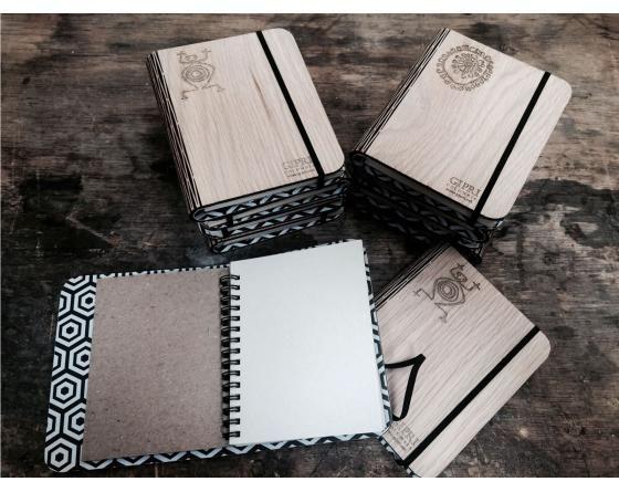 libreta-de madera A7 con cuadernillo papel reciclado. Hecha a mano y terminados naturales. Tapa de madera contrachapada y acabado natural con goma laca y ceras. Banda resorte para cierre de las contratapas. Bisagra corte láser estilo rejilla. Cuadernillo de 80 hojas ralladas o cuadriculadas. Bolsillo sujetador en la contra solapa de la carátula.  http://www.dasdesign.co/shop/web/?view=product&locale=es_ES&product_id=13