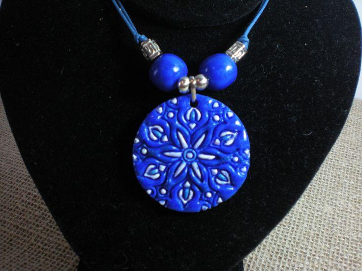 Colar confeccionado em cerâmica plástica em alto relevo azul e pintado de branco, acabamento em fio encerado azul e entremeios níquel.