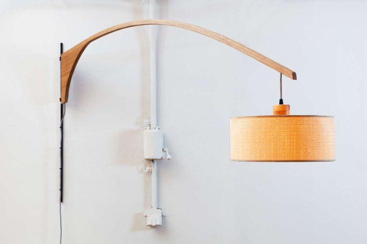 Li.Mod.Gun.W | Wall Lighting | d.Mod - Pivoting wall lamp made from a solid oak curve, fixed on a metal base. Its movement completes a little less than a semicircle of a 1,60m radius, while its fabric cable is safe within the length of the curve. It comes with a variety of options for both the lamp-shade and fabric cable.