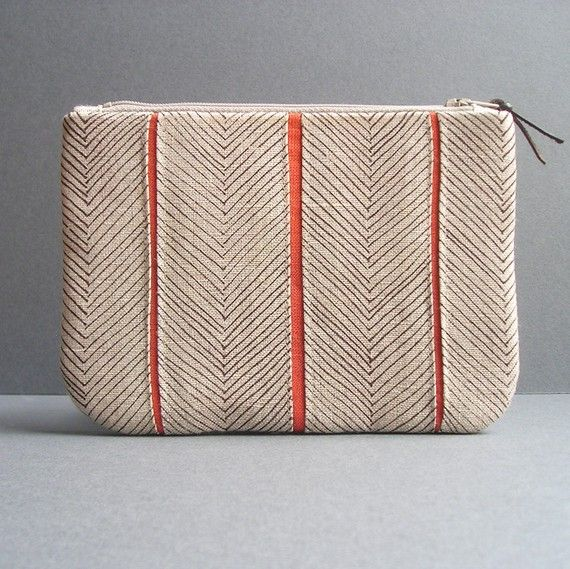 Sveika Essentials Clutch Carefully constructed in beautiful linen, the Essentials Clutch features our hand-drawn, herringbone print in chocolate with persimmon accents and lining. The lining includes a slip pocket for keeping your credit cards or cash in place. Hidden layers of thick canvas keep the clutch structured and sturdy for holding all your essentials.
