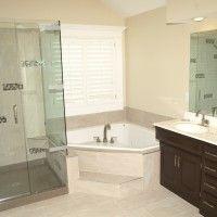 Interior. corner white  Bathtub   connected by glass shower room and black wooden bathroom vanity on the floor. Modern Design Of Small Corner Bathtub For Soaking