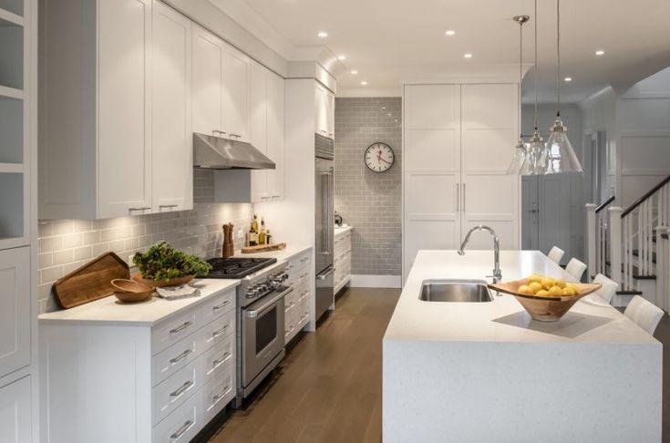 Wite kitchen with gray subway tile backsplash. Kitchen with glass pendant lights over white kitchen island