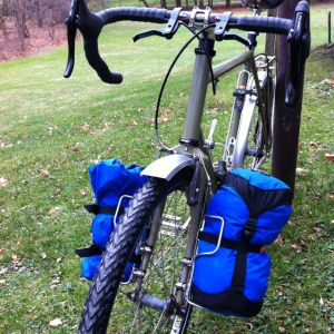 Even when I am traveling fairly lightly, I prefer to have a bit of weight in the front to balance the load.I've thus been experimenting with Salsa's Anything cages on my Surly Long Hau…