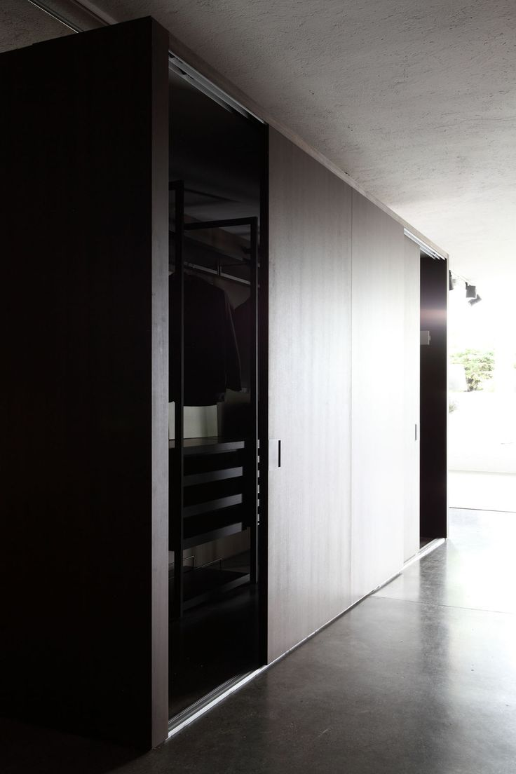 SHIFT sliding door / partition system by Porro Italy. Shown in smoked eucalyptus, closing in the CABINA walkin closet by Lissoni.