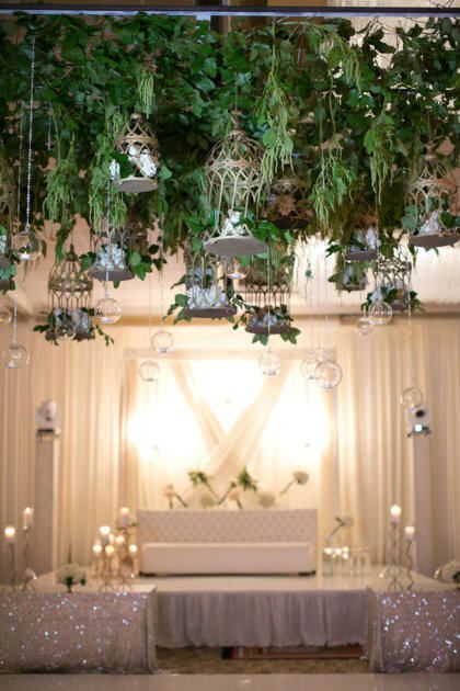 We are obsessed with this hanging greenery and floral installation with birdcages and crystal globes! Nimisha and Neal's day looked like it popped right off the pages of a storybook! Photo by J'adore Love Photo and Cinema #thebridesofok #oklahomabrides