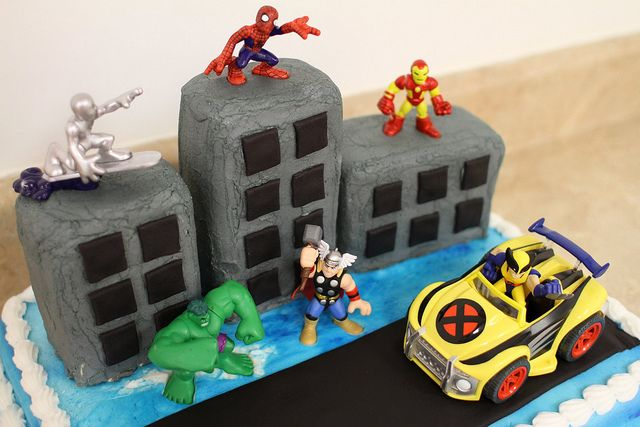 superhero cake.  buildings on top of cake are made with rice krispie squares  marshmallow fondant?