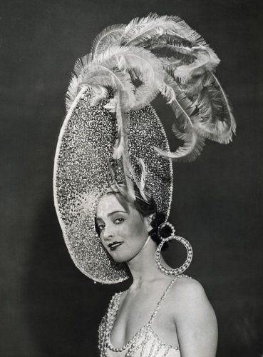 Onbekend   Dames hoeden. Mode uit Londen. Revue. Portret van een model met een grote hoed met struisvogelveren en parels, welke te zien is in de cabaretshow 'Magic Nights', geproduceerd door de heer Cochran. Engeland, april 1932.