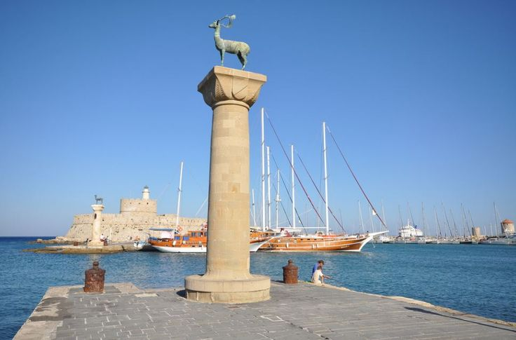 The Entrance To Mandraki Harbor in Rhodes. This is where The Colossus is said to have been standing centuries ago!  https://theislandofrhodes.com/the-city-of-rhodes-in-greece