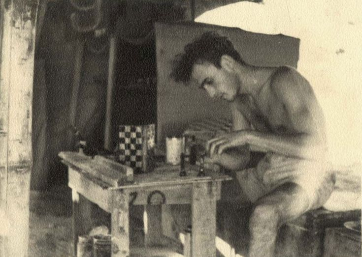 Aryeh Klein carving chess pieces in front of his tent in the detainment camp in Cyprus