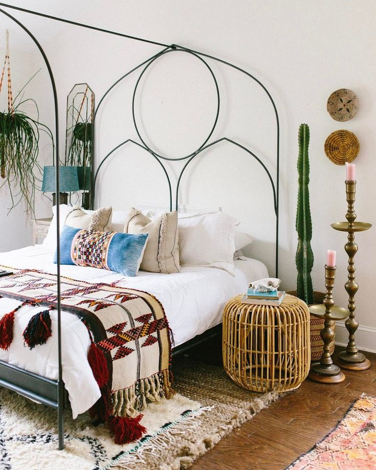 Bohemian Bedroom With Large Black Metal Frame Bed + Lots Of Eclectic Fabric Throws, Pillows And Rugs
