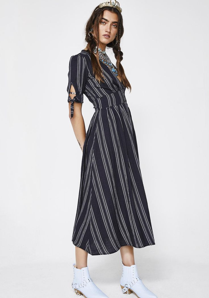 Lira Clothing Maverick Midi Dress cuz ya keep it easy breezy, bb. Do it your way in this flowy midi dress that has super cute knotted sleeves with a plunging neckline and pretty front buttons down the front.