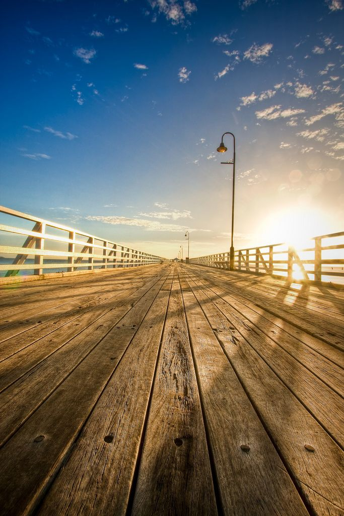The sun peeks over Shorncliffe Pier, Brisbane, Australia.