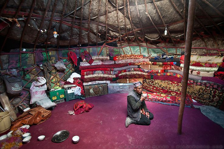 The interior of a yurt with a man drinking tea..Blankets filled with yak and sheep wool pile up against the inside wall of the yurt to insulate it from the constant winds. The floor carpet - bartered against 2 sheep - was acquired by Toorsoon in the lower valleys of Pakistan, a 10 days round trip leading over a 5000m pass. The wooden poles - over hundred years old - are handed over, generation after generation...At the Kyrgyz settlement of Bozoi Gumbaz, before Chaqmaqtin lake, Amon Boi's…