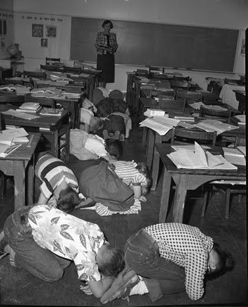 Duck and cover and don't look at the blast -School nuclear bomb drill during the Cold War.