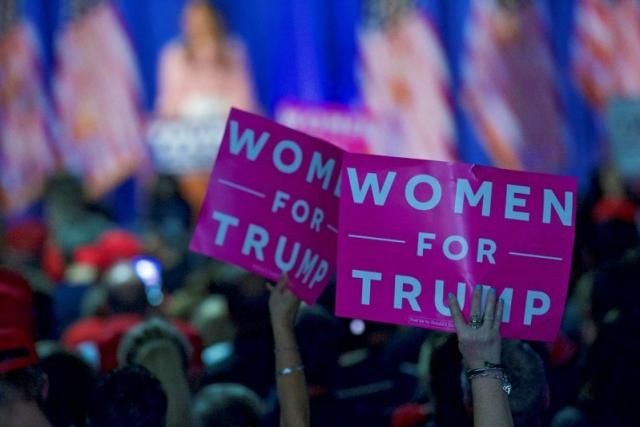 """FILE PHOTO: Supporters wave """"Women For Trump"""" posters while Melania Trump, wife to the Republican Presidential nominee Donald Trump, holds an event at Main Line Sports Centre in Berwyn, Pennsylvania, U.S. November 3, 2016.  REUTERS/Mark Makela/File Photo"""