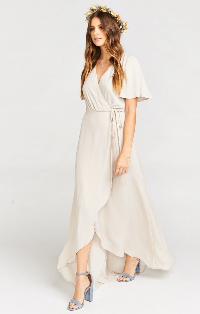 Sophia brightens the room wherever she goes.  Her delicate flutter sleeve and cinched waist offer a flirty option for your bridesmaids.  Ties at the side with a high-low wrap around slit that elegantly covers all for the ceremony but can cut loose on the dance floor at the reception.     *MADE IN THE GORGE USA* *100% Poly *Lined as Mini Dress  *High/Low Cut  *Flutter Sleeve  *Wrap around, tie dress