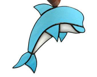 Zijn dolfijnen vissen of dieren? Wie kan het iets schelen! Ze zijn grappig, goedhartig en grillige, en dat is het belangrijkste idee. Hier is gekleurd glas dolfijn suncatcher in aqua blauw en wit kleuren met een zwarte afwerking. Het glas decor de ruimte in uw huis zal sieren, zal het helderder maken. Het is zowel perfect als venster opknoping decoratie of muur kunst decor.  Het meet ongeveer 20 cm van hoofd aan staart en 10 cm breed (ca. 8 x 4)…