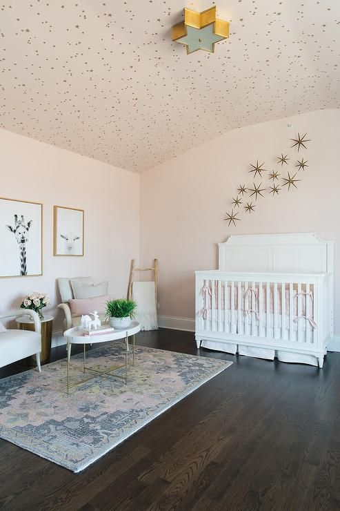 A white nursery crib dressed in white and pink bedding sits beneath gold sunburst wall decor mounted to a pale pink wall under a ceiling covered in Cole & Son Whimsical Stars Wallpaper illuminated by a Sophia Flush Mount.