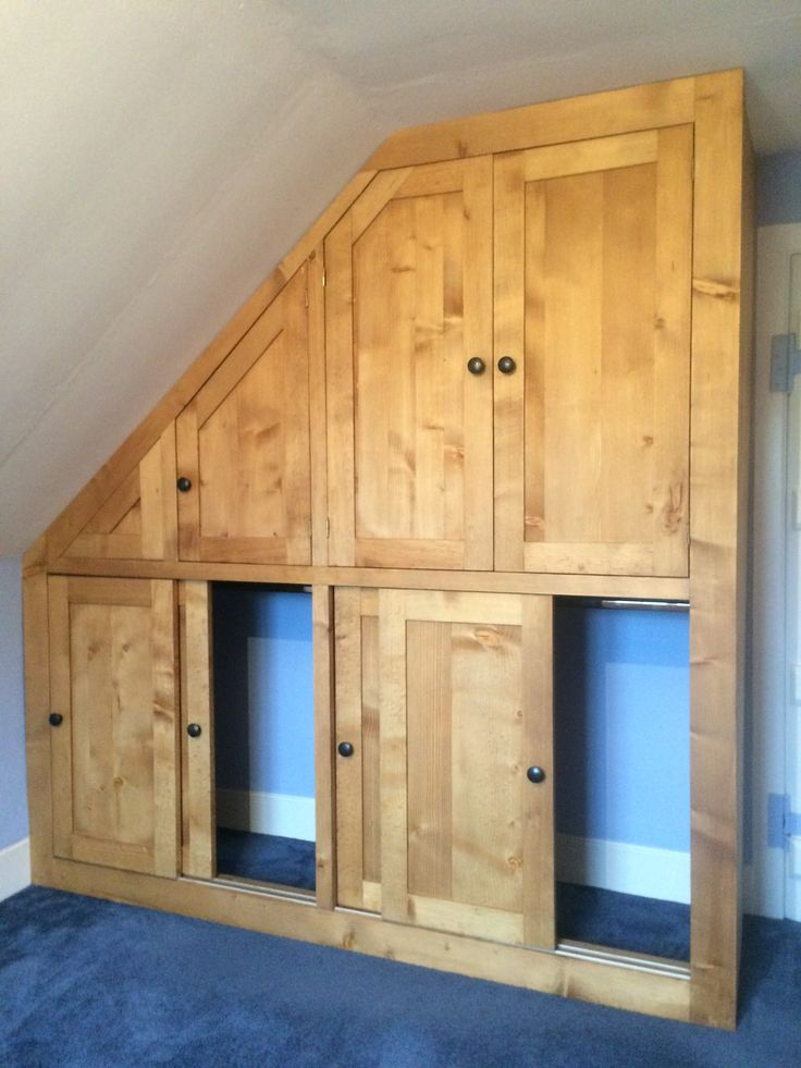 Sliding doors in this bespoke solid wood fitted wardrobe built into the  eaves of our customers