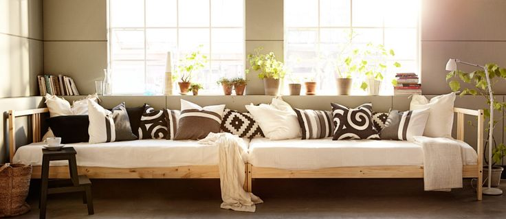 Two pine beds with thick mattresses and cushions in grey, white and black